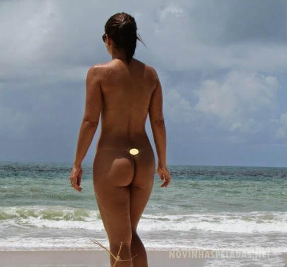 mulher nua na praia exibindo sua buceta linda